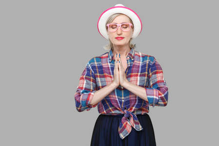 Portrait of calm modern stylish mature woman in casual style with hat and eyeglasses standing with palm hands, closed eyes, doing yoga pose exercises. indoor studio shot isolated on gray background. Reklamní fotografie