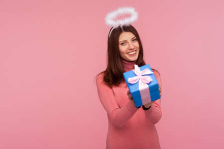 Angelic beautiful woman with brown hair and halo above head holding gift box and smiling, congratulating on holiday, giving present. Indoor studio shot isolated on pink background