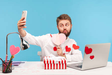 Trendy bearded man blogger sitting on desk with laptop all covered with heart shaped stickers and posing at camera pressing lips in kiss. Indoor studio shot isolated on blue background
