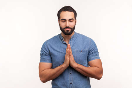 Calm and relaxed bearded man in blue shirt pressing hands together and smiling, meditating and opening his mind, standing with closed eyes. Indoor studio shot isolated on white background