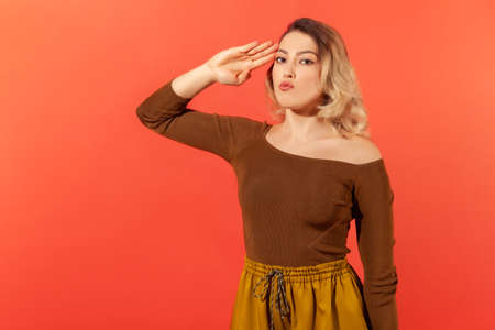 Portrait of responsible serious woman with blonde hair in brown blouse saluting commander, listening order with obedient expression. Indoor studio shot isolated on red background