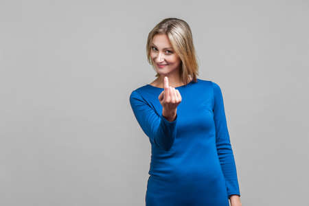 Come here! Portrait of attractive woman in elegant tight blue dress making beckoning gesture, inviting to come, flirting and looking playful. indoor studio shot isolated on gray background