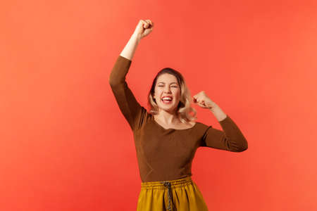 I am winner! Portrait of happy and smiled pretty woman who raised her hands up with clenched fists. Demostrates victory, success, good news, triumph. Indoor studio shot isolated on red background