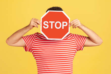 Unknown anonymous man in red striped t-shirt hiding his face behind red stop sign board, scared victim of humiliation and violence. Indoor studio shot isolated on yellow background Stock Photo