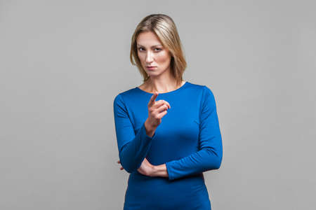 Bossy caution. Portrait of serious angry woman in tight blue dress pointing finger, showing warning gesture at camera, alarming to be careful. indoor studio shot isolated on gray background