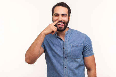 Funny comical man with beard picking finger to nose and showing tongue, looking at camera with smile, having fun, fooling around, bad manners. Indoor studio shot isolated on white background