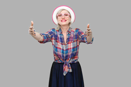 Portrait of happy modern stylish mature woman in casual style with hat and eyeglasses standing giving hands to hug and looking with toothy smile. indoor studio shot isolated on gray background. Stock fotó
