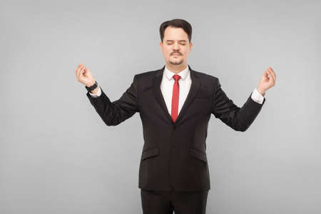 Businessman closed eyes, standing and doing yoga pose to calm down and stop hating the boss you need to do yoga. isolated on gray background. handsome businessman with black suit and mustache.