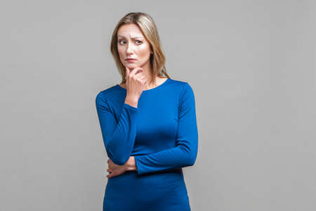 Portrait of confused puzzled woman in tight blue dress standing holding her chin and looking aside while thinking intensely, having doubts suspicion. indoor studio shot isolated on gray background