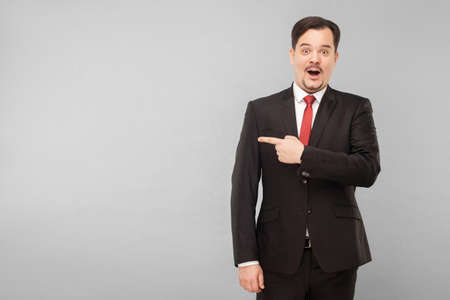 Amazement businessman pointing finger to copy space for your advertisement. Indoor, studio shot, isolated on gray background