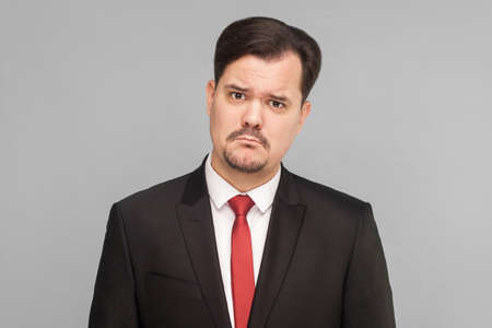 Sad, looser businessman, crying, looking at camera and hope. Need a new job and money. isolated on gray background. handsome businessman with black suit, and mustache looking at camera.