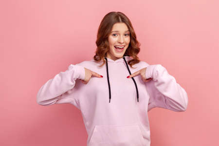 Portrait of cheerful curly haired teenage girl in hoodie pointing fingers at herself and surprisingly smiling at camera, wonder. Indoor studio shot isolated on pink background
