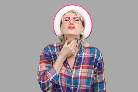 Throat pain illness or flu. Portrait of sick modern stylish mature woman in casual style with hat and eyeglasses standing and holding her painful neck. indoor studio shot isolated on gray background