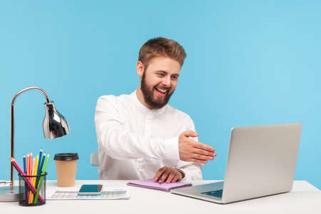 Friendly positive man hr manager conducting online interview, holding out hand to laptop display to greet new employee, preparing questions in notepad. Indoor studio shot isolated on blue background