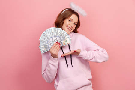 Portrait of successful curly haired teenage girl in hoodie with halo on head showing bunch of dollar banknotes and sincerely smiling, charity campaign. Indoor studio shot isolated on pink background 版權商用圖片