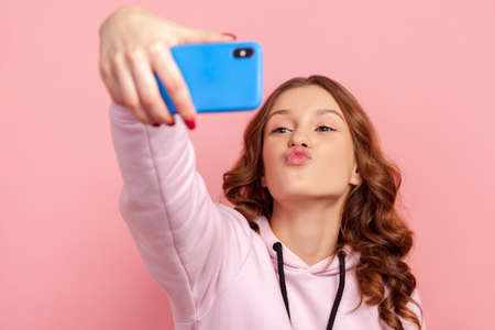 Portrait of cute curly haired teenage girl in hoodie sending air kiss on smartphone camera while communicating by video call or streaming vlog. Indoor studio shot isolated on pink background
