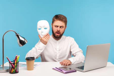 Bearded man office worker looking at white face mask in his hand with suspicion, hiding his identity, spying undercover, corruption. Indoor studio shot isolated on blue background 版權商用圖片