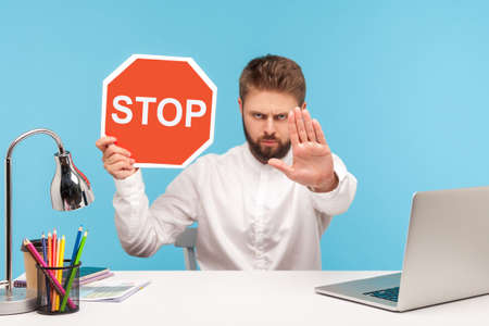 Access denied. Bossy bearded man sitting at workplace with laptop showing stop gesture with hand and holding red stop sign board, enter is restricted. Indoor studio shot isolated on blue background 版權商用圖片