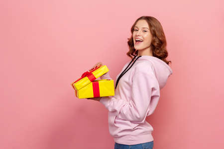 Profile of joyous curly haired teenage girl in hoodie standing with opened gift box, looking at camera with toothy smile, satisfied with holiday present. Indoor studio shot isolated on pink background 版權商用圖片