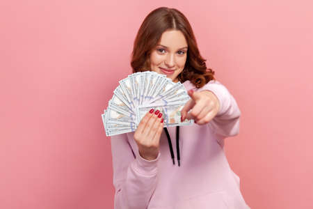 Portrait of joyful curly haired teenage girl holding bunch of dollar banknotes and pointing finger on camera, hey you gesture, winner. Indoor studio shot isolated on pink background 版權商用圖片