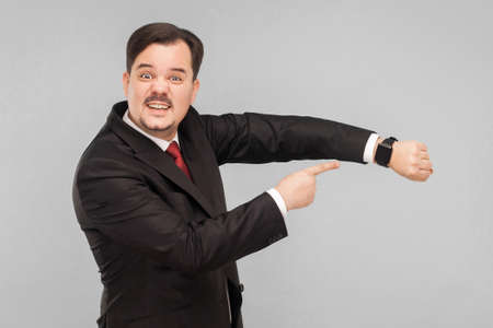 Not have a many time, hurry please! indoor studio shot. isolated on gray background. handsome businessman with black suit, red tie and mustache looking at camera.