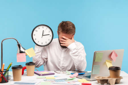 Tired busy man leaning head on hand holding big wall clock, sitting at workplace all covered with sticky notes, overworking, professional burnout. Indoor studio shot isolated on blue background
