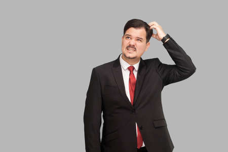 Business strategy and work concept. Puzzlement ceo planning what to say on the board of directors. studio shot, isolated on gray background. handsome businessman with black suit, and mustache.