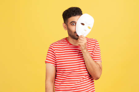 Funny crazy man with beard in striped t-shirt peeping out white face mask, hiding his real feelings, pretending to be another person. Indoor studio shot isolated on yellow background Banque d'images