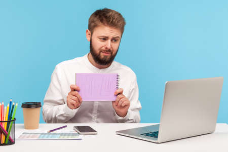 Tired overworked man office worker with beard holding showing notepad with help inscription at camera talking video call with boss, professional burnout. Indoor studio shot isolated on blue background