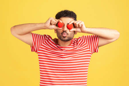 Bearded man in love in red striped t-shirt sending kiss holding toy heart near eyes, love confession, romantic relationships, fondness. Indoor studio shot isolated on yellow background Stockfoto