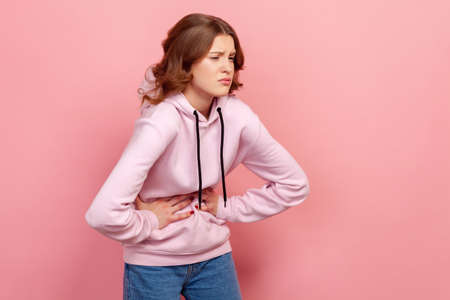 Portrait of brunette young female in hoodie hunching and touching her belly, suffering period cramps, abdominal pain. Indoor studio shot isolated on pink background Stockfoto