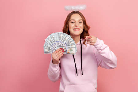 Portrait of happy curly haired teenage girl in hoodie with halo on head holding lot of dollars and pointing finger on camera, hey you gesture. Indoor studio shot isolated on pink background Stockfoto