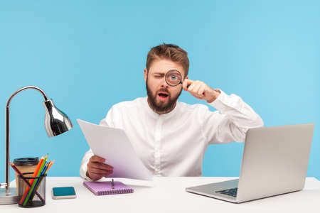 Attentive bearded man office worker holding loupe near eye making funny face expression, analyzing report data, working at research sitting at workplace. Indoor studio shot isolated on blue background