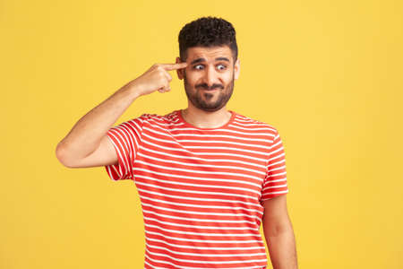 Crazy idea! Bearded man in red striped t-shirt showing stupid gesture, looking with condemnation and blaming for insane plan, dumb suggestion. Indoor studio shot isolated on yellow background
