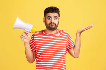 Puzzled confused man with beard in striped t-shirt shrugging shoulders holding in hands megaphone, cant find common language, communication problems. Indoor studio shot isolated on yellow background