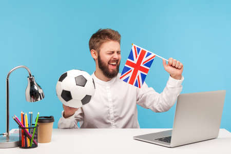 Cheerful bearded man football fan holding flag of great britain and classic soccer ball, sitting at workplace with laptop and watching match. Indoor studio shot isolated on blue background