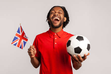 Extremely happy man with british flag and black and white ball wearing red casual style T-shirt, cheering for his favorite team, rejoicing to win. Indoor studio shot isolated on gray background. Stockfoto