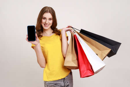 Portrait of happy smiling teenager girl in yellow T-shirt holding cell phone and shopping bags, advertising online store on mobile device. Indoor studio shot isolated on gray background.