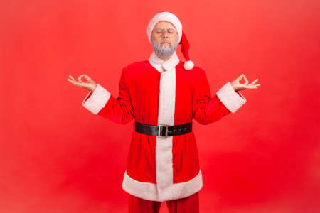 Elderly man with gray beard wearing santa claus costume meditating with closed eyes, feeling calm relaxed with peaceful mind, yoga practice. Indoor studio shot isolated on red background.