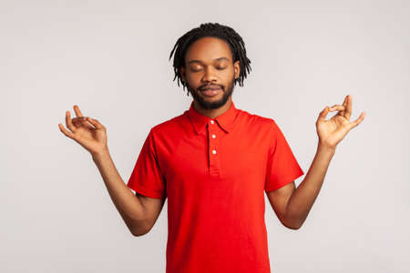 Portrait of relaxed bearded man with dreadlocks wearing red casual style T-shirt, standing with raised arms and doing yoga meditating exercise. Indoor studio shot isolated on gray background. Stock Photo
