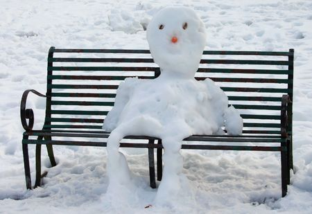 Snowman sitting on park bench 免版税图像