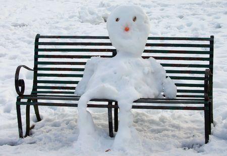 Snowman sitting on park bench Stock Photo