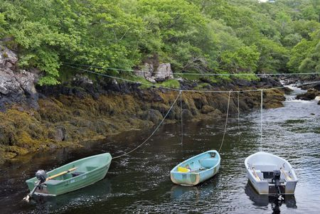 tethered: three tethered boats on a river at Badachro, NW Scotland