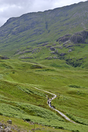 A group of hikers on a path in Glencoe, North West Scotland
