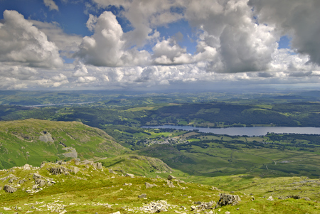 Coniston & Coniston Water seen from approach to Coniston Old Man. Windermere can be seen in the distance. The sky is filled with developing Cumulus clouds