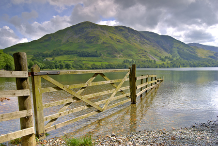 A partially submerged fence on the shore of Buttermere in the English Lake District