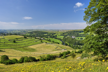 A view of the Ribble valley from the flower meadows of Lancliffe Scar. The river Ribble can be seen flowing past fields seperated by dry stone walls Stock Photo