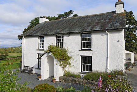 A Typical whitewashed country cottage set in open countryside in the English Lake District