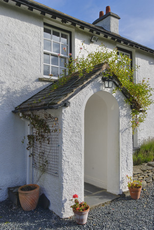 the porch of a typical whitewashed country cottage set in open countryside in the English Lake District Stock Photo