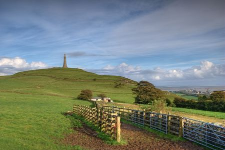 bluer: The Hoad monument on Hoad Hill above Ulverston, Cumbria, England. Dry stone wall, gates, and feeding trough in the foreground